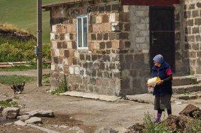 Village de Vladimiovka - une femme barrate le beurre à la main